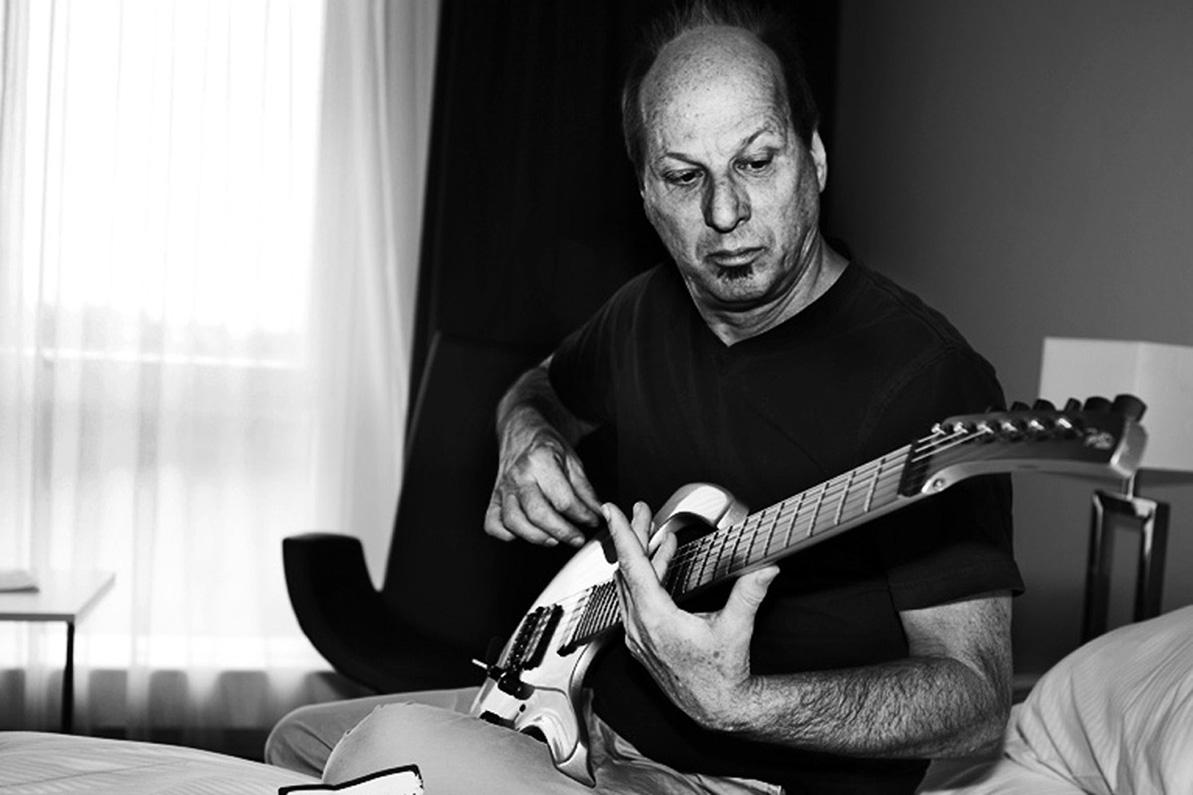 Guitaristen Adrian Belew siddeer på hotelværelset og skifter strenge inden koncerten i 2016